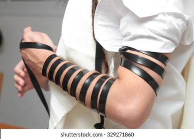 A religious orthodox Jew with arm-tefillin on his left hand prays A jewish man is preparing the tefillin