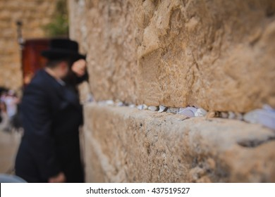 Religious orthodox jew praying at the Western Wall in the old city of Jerusalem Israel. There are notes to God in the cracks between the bricks.