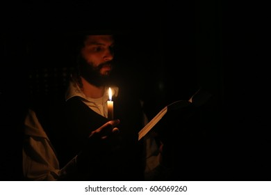 A religious Orthodox Jew preforms the ritual of Bedikas Chometz. Bedikas Chometz is a tradition in which Jews search for and burn all leavened bread prior to the onset of Passover.