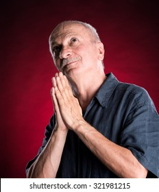 Religious senior man praying to god on a dark red background
