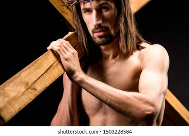 religious and shirtless man in wreath with spikes holding wooden cross isolated on black