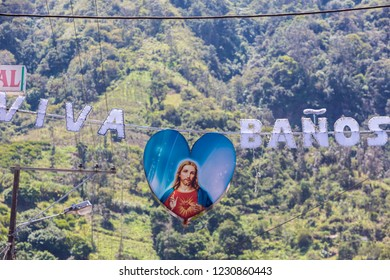 """Religious sign suspended to a cable with the greeting words """"Viva Banos"""" written is Spanish in Ecuador."""