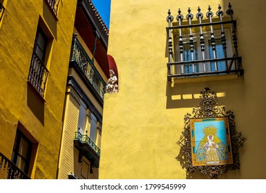 Religious statue in corner niche of a building; sidestreet of Seville, Spain