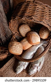 Religious still life of loaves of bread, fishing net, basket and two fresh fish