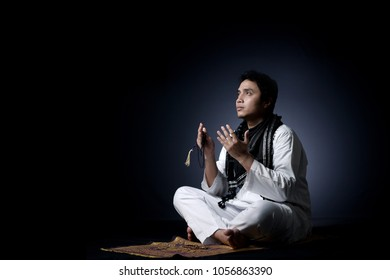 Religius moslem man praying isolated in black backgorund