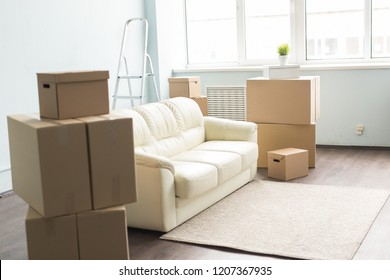 Relocation, new home and real estate concept - Moving boxes and sofa in empty room