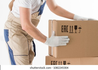relocation services concept. Mover's hands In uniform carrying cardboard Box. Loader puts cardboard boxes isolated on white background. Worker mover unloading paper box. Delivery man.