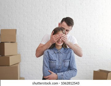 Relocation. Surprise. Happy couple. Man clothing eyes of woman.