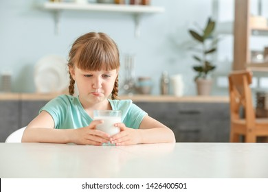 Reluctant little girl with glass of milk at table