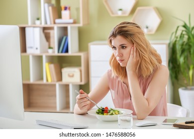 Reluctant woman with healthy vegetable salad in office
