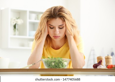 Reluctant woman with healthy vegetable salad in kitchen