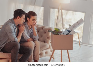 Rely on me. Displeased upset young woman sitting on sofa and propping her head with hand while her careful boyfriend hugging and calming her down