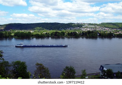 Remagen / Germany - May, 12, 2019: view from above over the Rhine river (Romantic Rhine). Landscape with rolling hills, villages and a cargo boat. Nice sunny day with blue sky and some clouds.