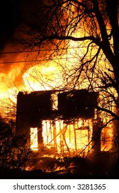 The remaining frame of a house on fire at night