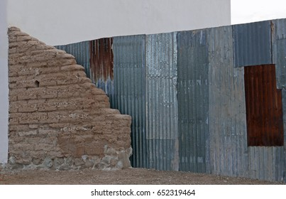 Remains of an adobe brick wall next to a corrugated sheet metal fence