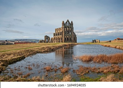 Remains of an ancient gothic english abbey ruins with reflection in lake water