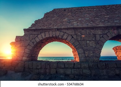 Remains of the ancient Roman aqueduct in ancient city Caesarea at sunset. Israel.