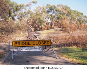 Remains of a burned down foot bridge and a warning sign after bush fire in an suburban area of Knox City in Melbourne east