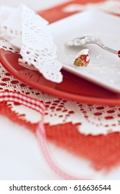 Remains of cake with a cream and strawberries in white and red plates on napkin on wooden board