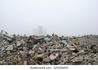 The remains of concrete fragments of gray stones on the background of the destroyed building in a foggy haze. The impact of the destruction. Background.