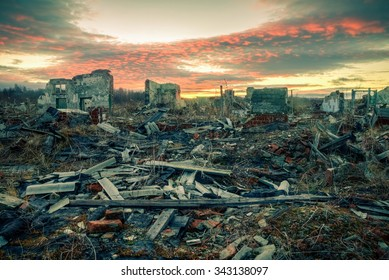 The remains of destroyed houses at sunset. Apocalyptic landscape