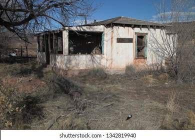 Remains of an falling adobe house that once had blue trim and whitewashed walls on the high plains of New Mexico