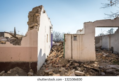 Remains of hurricane or earthquake aftermath disaster damage on ruined old houses with collapsed roof and wall