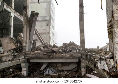 The remains of a large building destroyed in a foggy haze. Concrete piles of the building frame are prepared for demolition and disposal. Background.