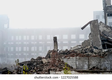 The remains of a large destroyed building with concrete pilings and scattered bricks with rebar against the frame of a large building in the fog. Copy space.