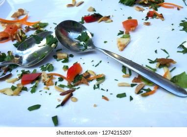 The remains of a meal are on a white plate. This includes tomato, pine nuts , carrot, slivered almonds, parsley and bread. Two silver spoons are on the  plate.