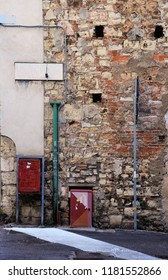 "Remains of medieval wall with street name and old ""cassetta di servizio postale"" (postal service box) made of red and scratched metal. Brescia, Italy."