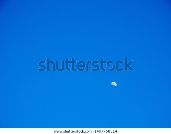 Remains of the moon in a blue sky during the day