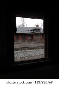 Remains of an old abandoned brick train station seen from inside another abandoned structure. Dark edges.