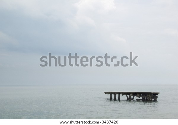 Remains of old dock in lake - calm before the storm