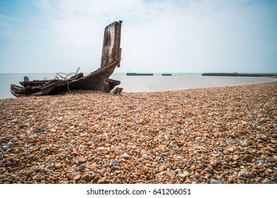 Remains an old wooden fishing boat on stony beach in Hastings, East Sussex, UK