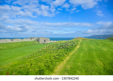 Remains of Peel Castle wall constructed by vikings at Peel hill covered with green grass and beautiful ocean of Isle of Man in background