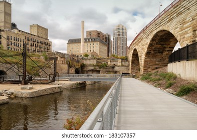 The remains of ruins now converted to a park with a boardwalk contrasting with the high-rise office building and apartment complex in the background, in downtown Minneapolis
