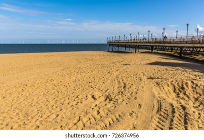 The remains of Skegness pier, UK pointing out seaward towards the wind farm on the horizon in summertime