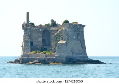 The remains of a stone tower cover a small rocky island in a calm ocean. Arches and stairwells are visible. The sky is blue, and some seagulls are flying past.