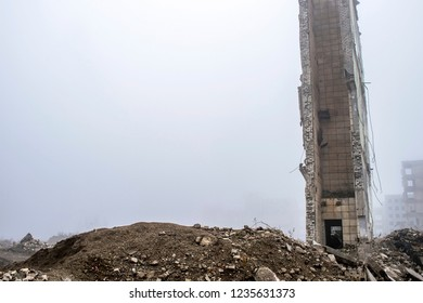 The remains of the wall of a large destroyed building against the background of other destroyed buildings in a foggy haze and a pile of rubble in the foreground. Copy space.