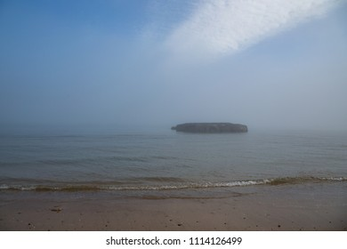 Remains of a WWII Mulberry harbour in the mist at Arromanches in Normandy; the Mulberry was an allied initiative to provide an artificial harbour to land supplies.