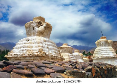 remarcable scenic view, old white buddhist stupa (chorten) against the background of distant colorful mountain range and dramatic blue sky, Leh, Ladakh, Himalaya, Jammu & Kashmir, Northern India
