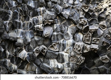 Remarkable hexagonal columnar basalt volcanic rock formations on a hillside in Hljodaklettar northern Iceland where human like faces appear in the stones