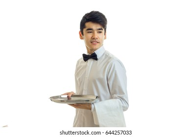 remarkable young waiter in a white shirt holding a tray, and the towel looks away and smiling