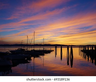 Remarkably colorful Lake Champlain sunset in Burlington, Vermont with wispy orange clouds reflected on the water. Boats and a pier in silhouette are also reflected at the end a beautiful autumn day.