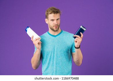 Remedies get rid of dandruff. Man hold two bottle shampoo violet background. Itchy scalp flakiness skin. Shampoo solve dandruff problem. Anti dandruff remedy. Alternative haircare remedies concept.