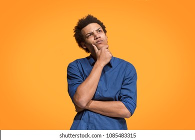 Remember all. Let me think. Doubt concept. Doubtful, thoughtful man remembering something. Young emotional afro man. Human emotions, facial expression concept. Studio. Isolated on trendy blue. Front