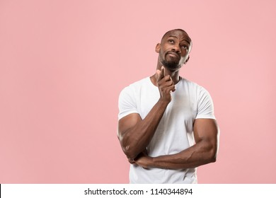 Remember all. Let me think. Doubt concept. Doubtful, thoughtful afro man remembering something. Young emotional man. Human emotions, facial expression concept. Studio. Isolated on trendy pink. Front
