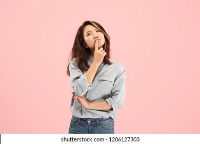 Remember all. Let me think. Doubt concept. Doubtful, thoughtful woman remembering something. Young emotional woman. Human emotions, facial expression concept. Studio. Isolated on trendy pink