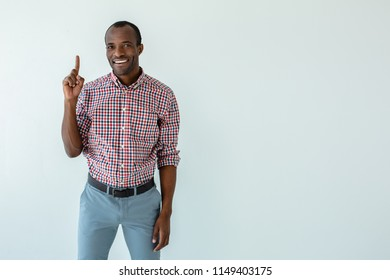 Remember it. Cheerful smiling afro american man making recommendations while standing against white background